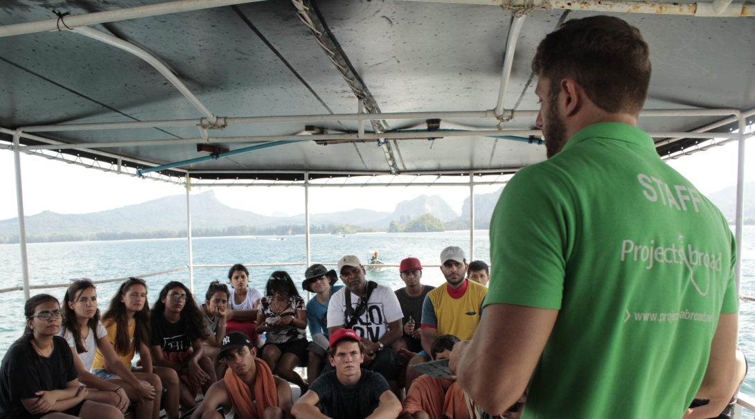 Conservation volunteers listening to their project supervisor about safety and rules while in Thailand
